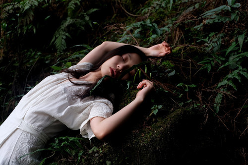 Woman sleeping on the forest ground