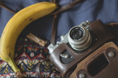 Retro photo camera, fruit and clothes