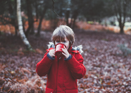 Kid drinking cocoa in nature