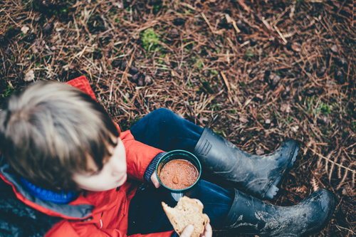 Kid eating beans in nature