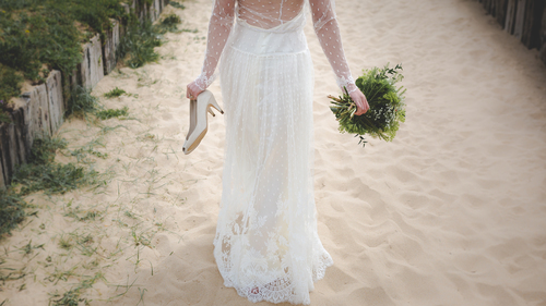 Bride walking in sand