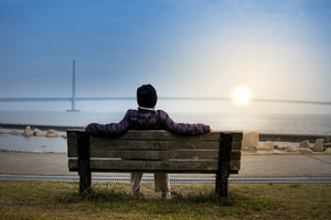 Man sitting on a bench watching sunset