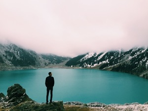 Man standing by the blue lake