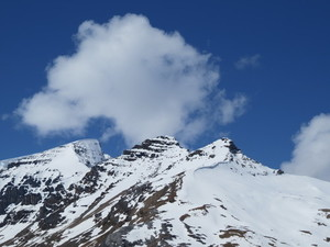Snowy mountain peak under big cloud