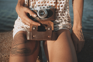 Girl with tattoo and photo camera