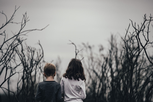 Boy and girl standing among trees
