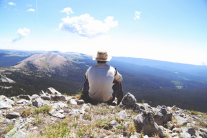 Guy with hat sitting on a mountain top