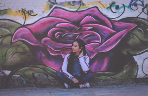 Girl sitting in fornt of graffiti