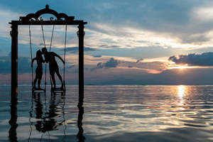 Man and woman swinging in the ocean