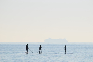 Three surfers in water