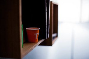 Coffee cup on book shelf