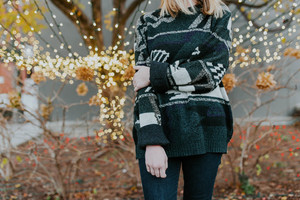 Girl in sweater with decorative lights behind