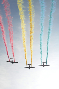 Three planes with colorful trail