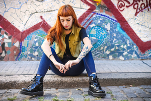 Punk fille assise sur un trottoir
