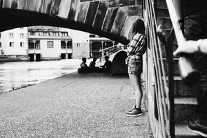 Girl by the canal and people under bridge