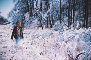 Girl walking through snowy forest