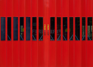 Red door with firefighters behind