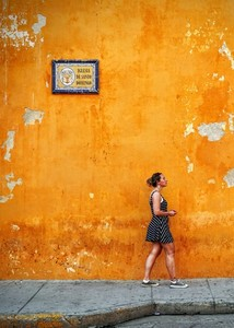 Lady in front of yellow wall