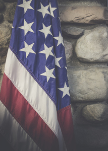 US flag in front of stone wall