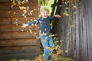 Boy running through leaves