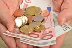 Euro bills and coins in a hand