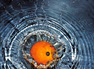 Orange falling into water bowl