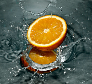 A half of orange splashes in the water