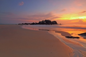 Long sandy beach with the colorful sunset