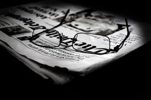 Newspaper with reading glasses
