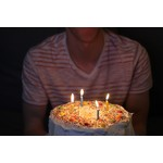Cake with lit candles and person behind