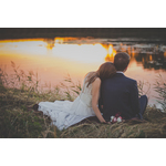 Bride and groom sit by pond